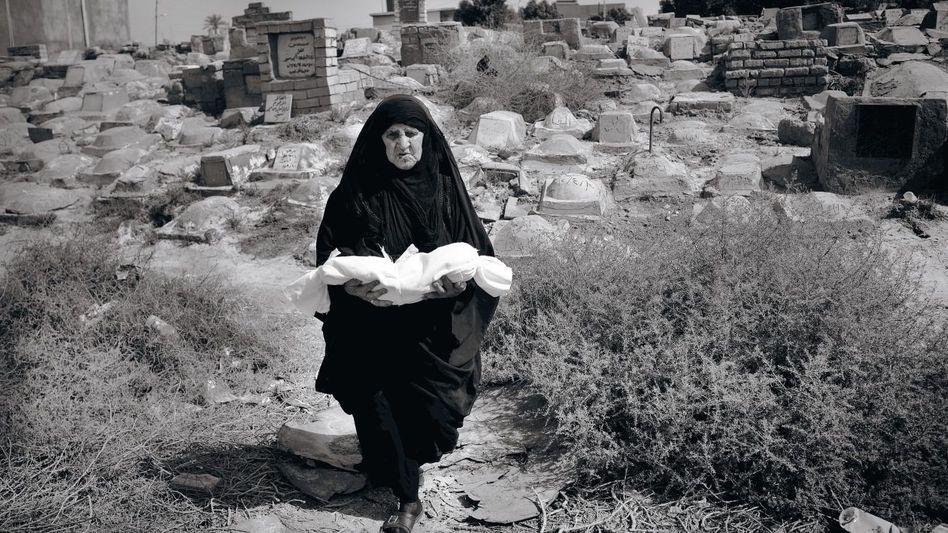 Eine Bestatterin mit einem toten Baby auf dem Kinderfriedhofvon Basra. Jeden Tag werden fünf bis zehn Kinder beerdigt.