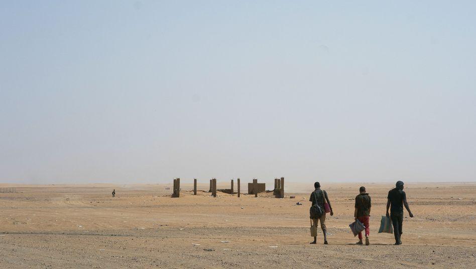 Weg durch die Wüste: Drei Männer auf dem Weg nach Algerien, nachdem sie den nigerianischen Grenzort Assamaka passiert haben