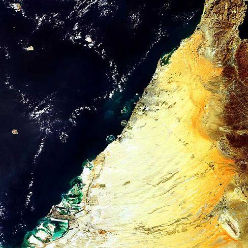 Blick aus dem All: Die größte erkennbare Insel in der Bildmitte ist Palm Jebel Ali, daneben die kleinere Palm Jumeirah, direkt über Jumeirah entstehen die World Islands.