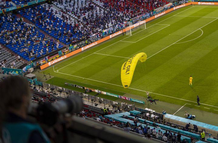 »Kick out Oil« steht auf dem Gleitschirm, mit dem ein Greenpeace-Aktivist in die Allianz-Arena trudelte