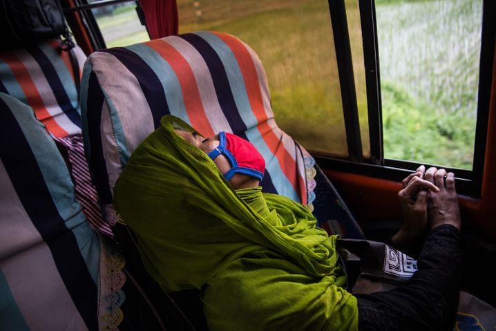 Tasnia Begum sleeps on the journey to her home village.