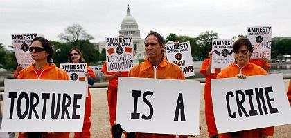Amnesty International protesters outside the White House mark President Obama's 100th day in office.