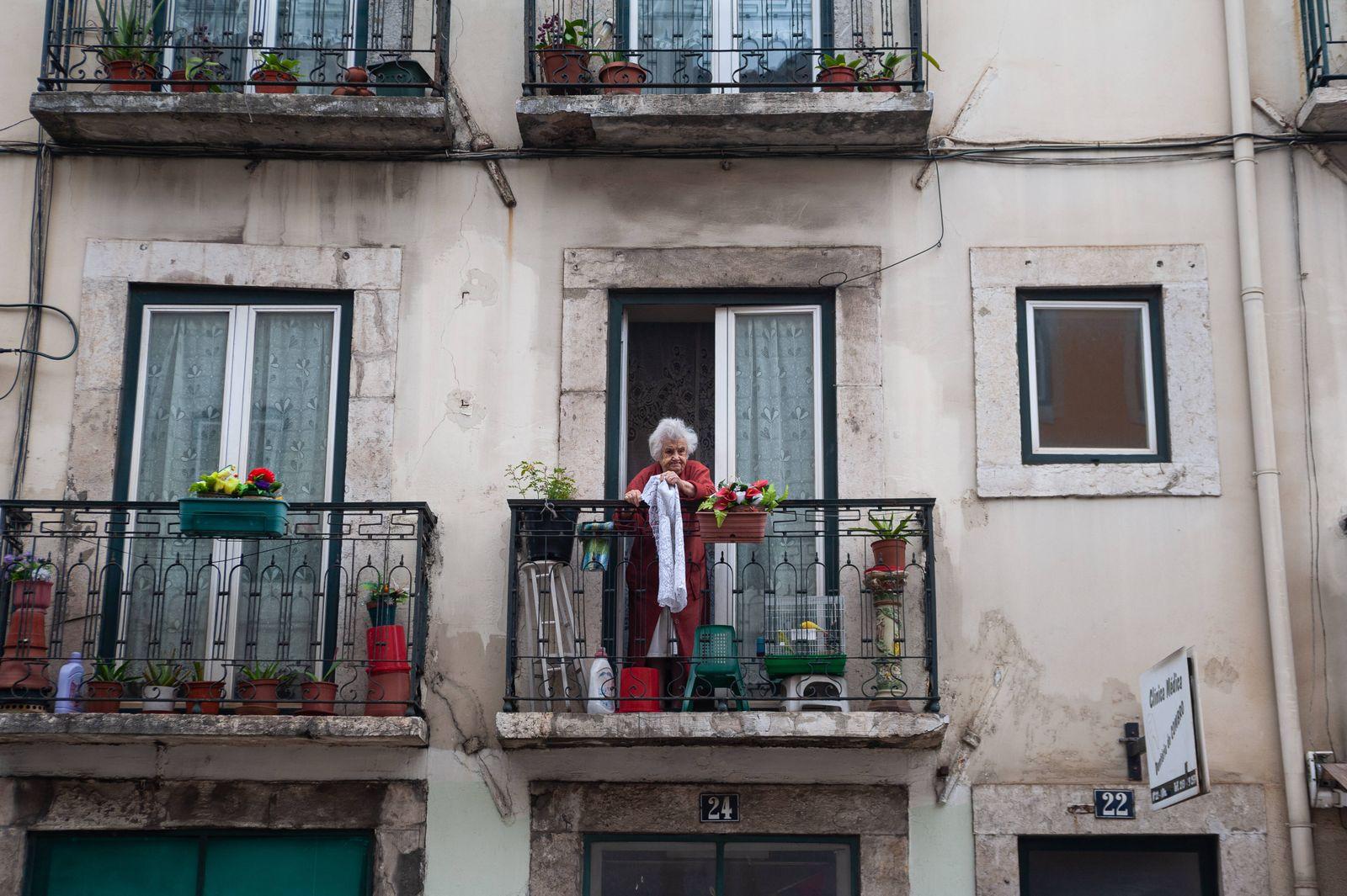 12.06.2018, Lissabon, Portugal, Europa - Eine alte Frau steht auf dem Balkon ihrer Wohnung in der Altstadt der portugies