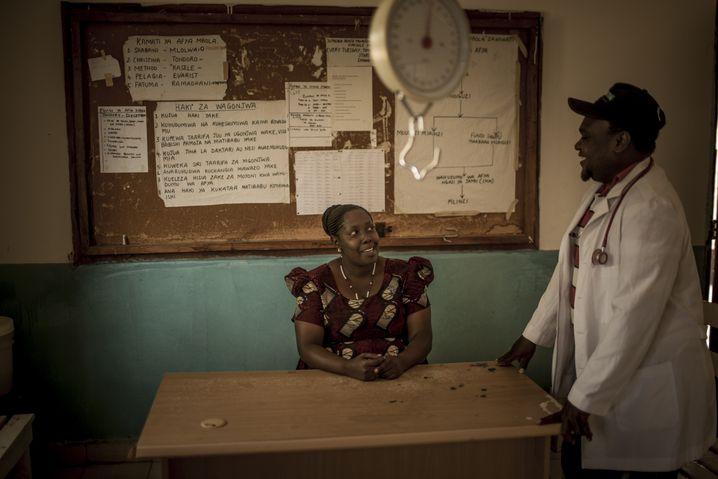 Damian Cleopa Kindole, the clinic's director, talks to the midwife Restitua Karele.
