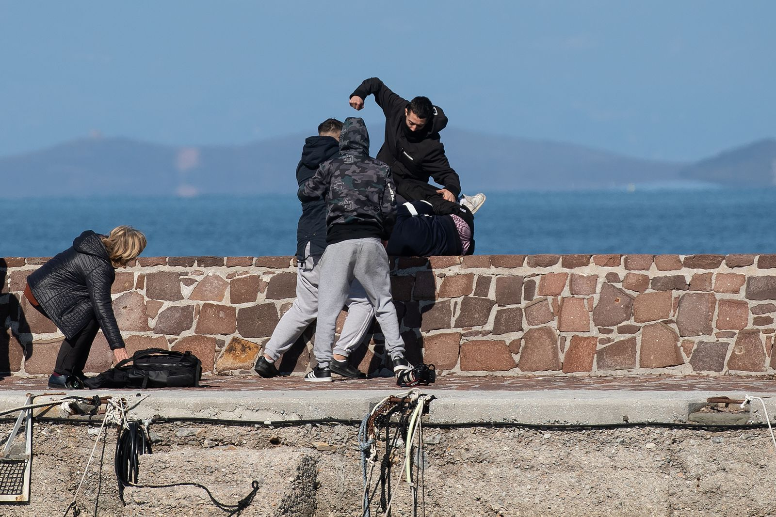 Locals who prevent migrants on a dinghy from disembarking at the port of Thermi beat a journalist on the island of Lesbos