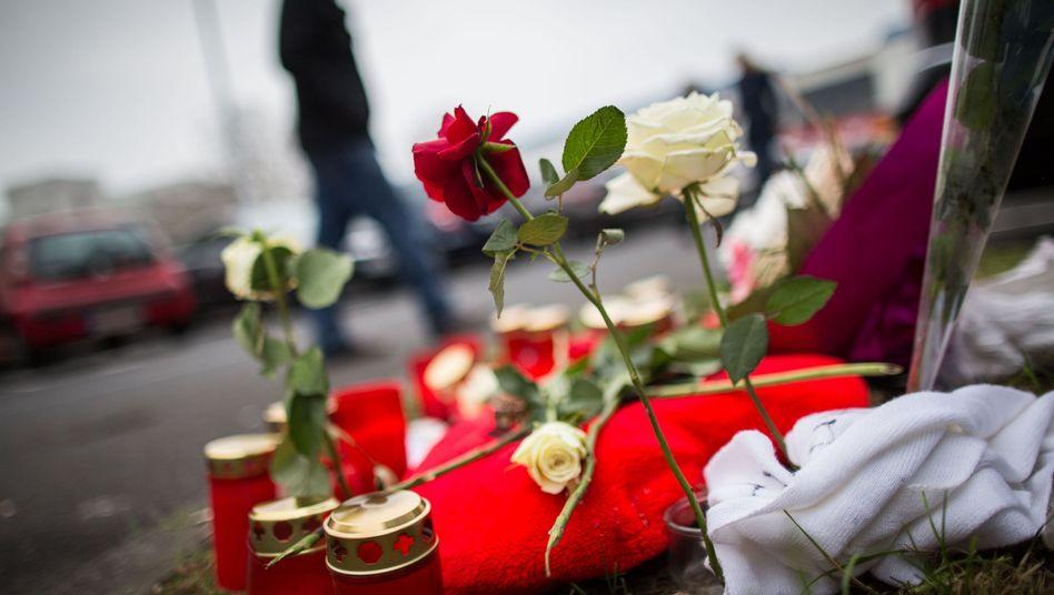 Tatort in Offenbach: Blumen und Kerzen auf Parkplatz vor Fast-Food-Lokal