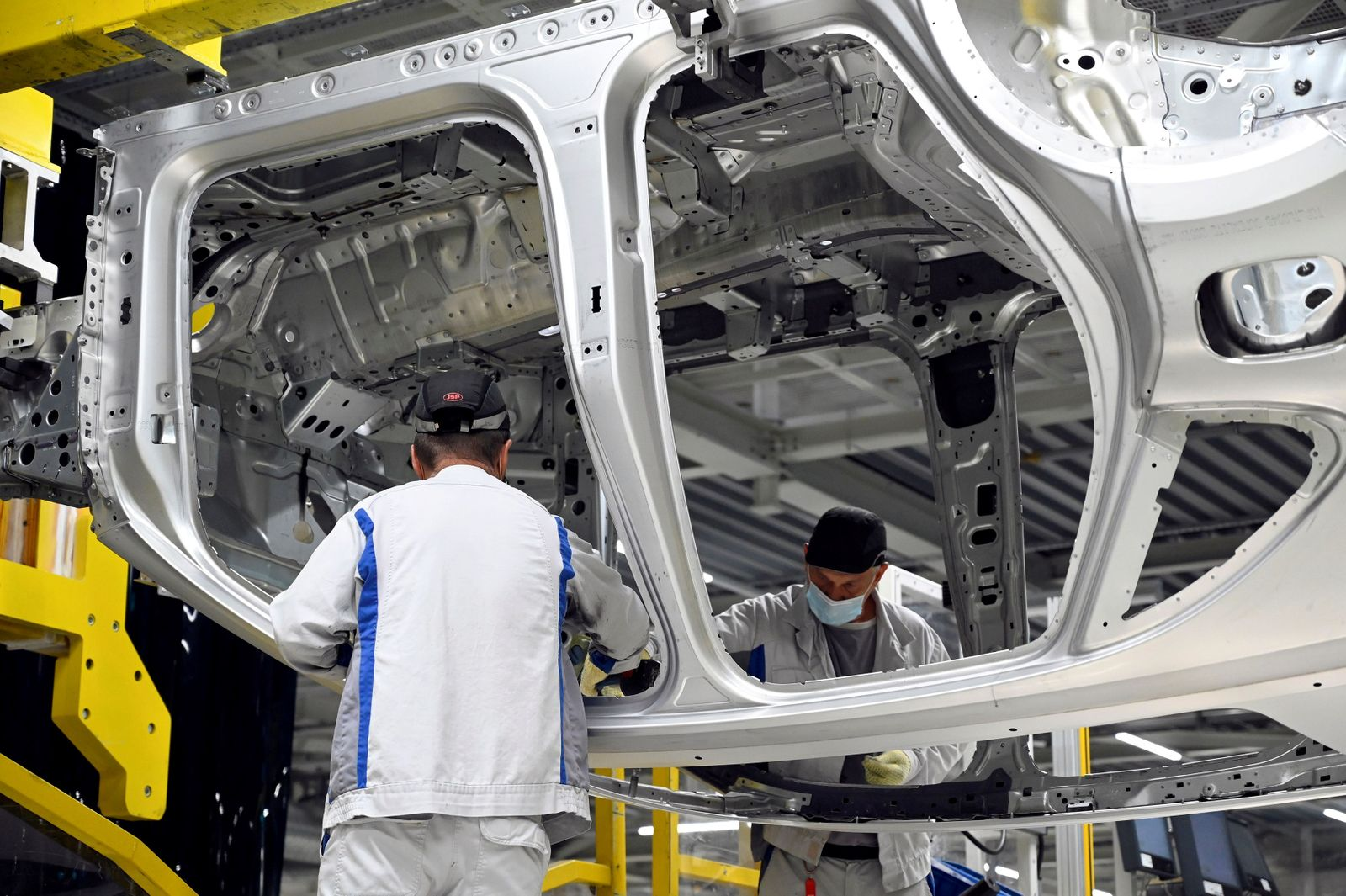 FILE PHOTO: Employees work on an assembly line as the Volkswagen construction plant reopens after closing down due to the coronavirus disease (COVID-19) outbreak in Bratislava