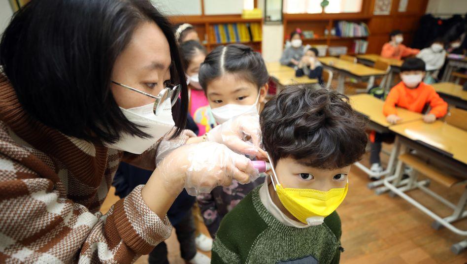 Corona-Check: Eine Lehrerin misst in China die Temperatur eines Grundschülers