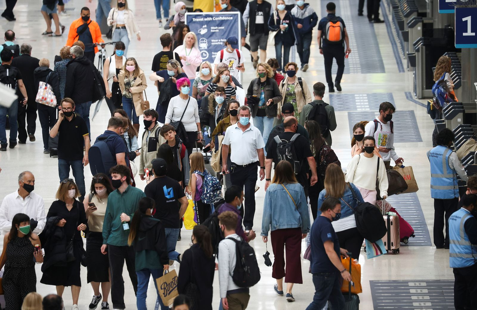People, some wearing protective face masks, walk through Waterloo Station, amid the coronavirus disease (COVID-19) pandemic, in London