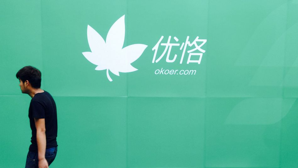 Passant vor Werbeplakat für okoer.com: Ziel ist Chinas Mittelschicht