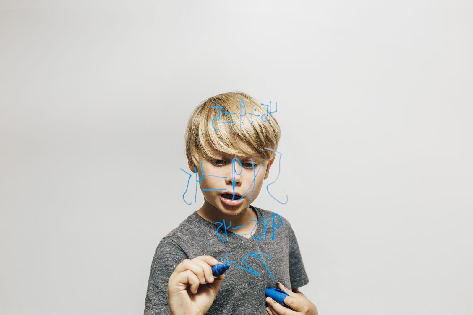 Boy writing equation onto glass wall