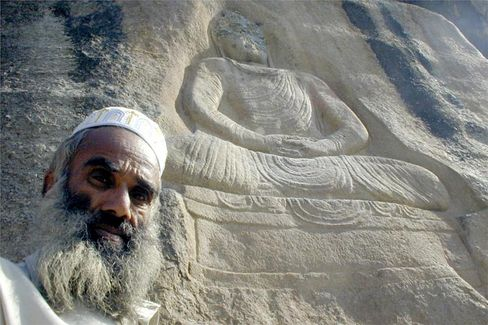 An Afghan local stands next to a rock effigy of the Buddha partly destroyed by militant Islamists.