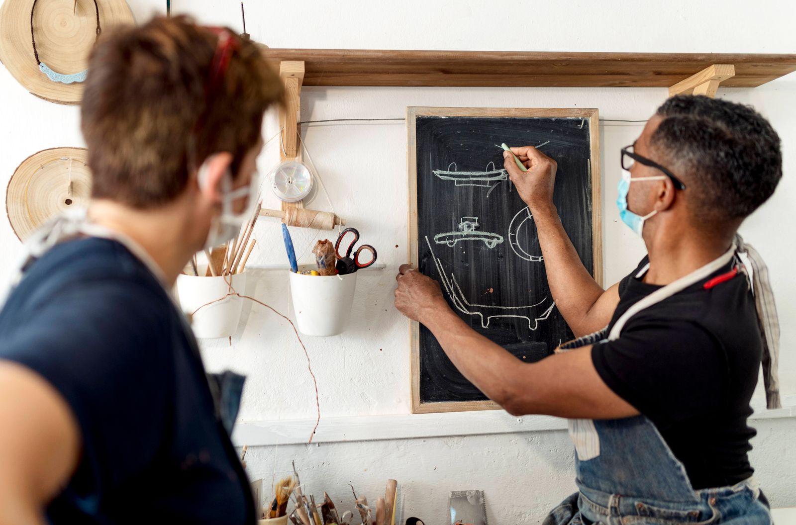 Woman looking at male potter drawing on blackboard in workshop model released Symbolfoto property released EGAF00731