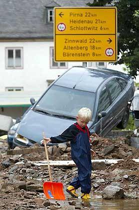 Ein kleiner Junge steht am Mittwoch inmitten von Trümmern in der durch die Hochwasserkatastrophe stark in Mitleidenschaft gezogenen sächsischen Kleinstadt Glashütte
