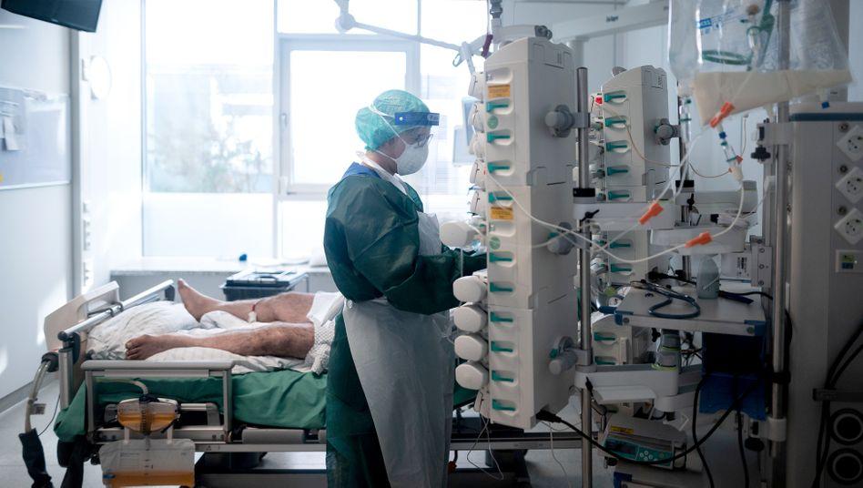 Eine Mitarbeiterin der Pflege betreut in Schutzausrüstung einen Corona-Patienten (Essen, Oktober 2020)