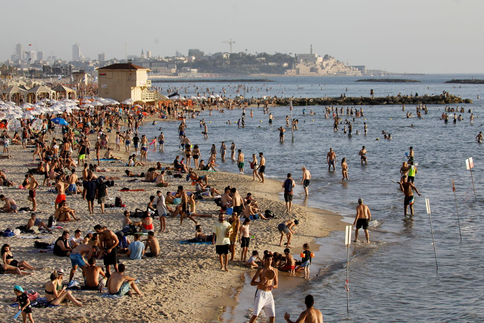 FILE PHOTO: Beachgoers hang out on the shore of the Mediterranean sea in Tel Aviv as coronavirus disease (COVID-19) restrictions ease in Israel