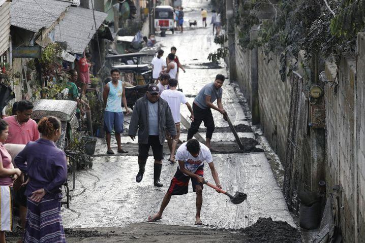Anwohner in Cavite reinigen eine Straße von dem Ascheschlamm