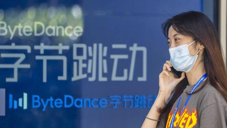 Handynutzerin in Shanghai vor der Zentrale von ByteDance, Anbieter der Video-App TikTok