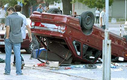 A car sits overturned on a street in Lublin, eastern Poland onSept. 11, 2005, after clashes between soccer hooligans and police.