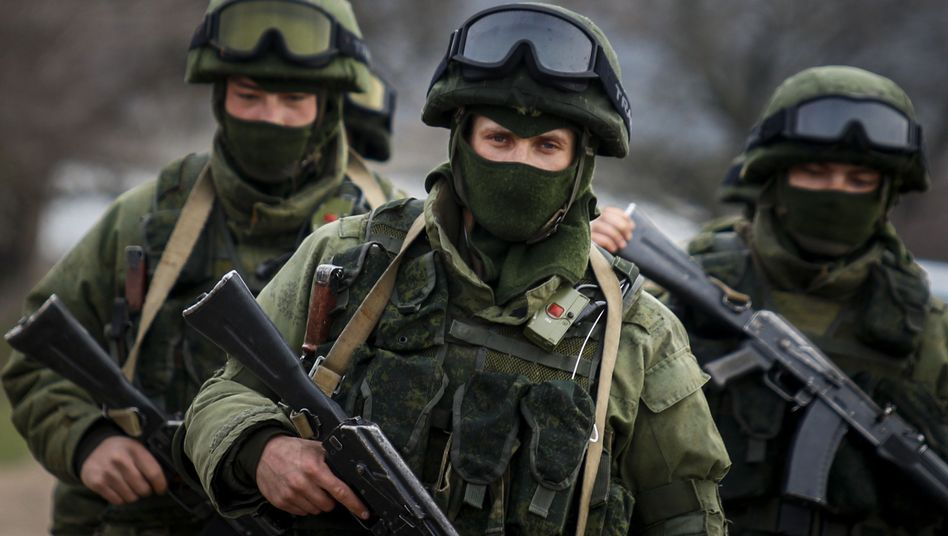 Armed men, believed to be Russian servicemen, march outside a Ukrainian military base in the village of Perevalnoye near the Crimean city of Simferopol.