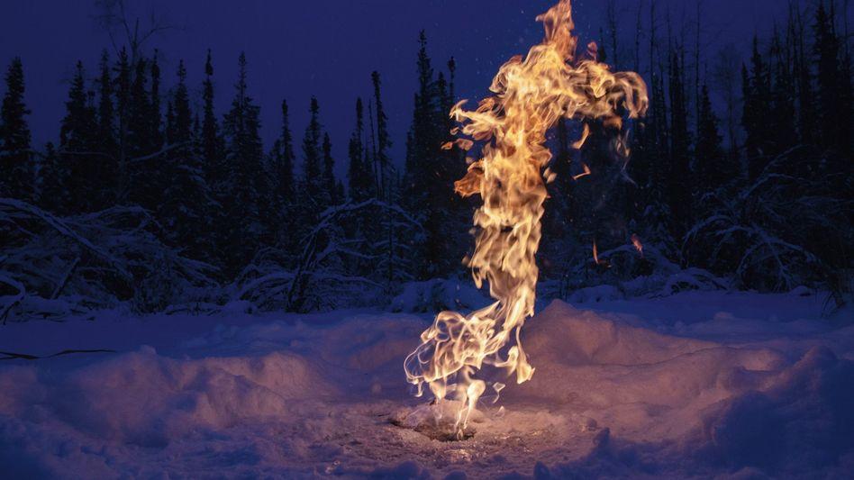 In Fairbanks, Alaska, haben Forscher ein Loch in die Eisschicht eines zugefrorenen Sees gebohrt und das darunter gefangene Methan sichtbar gemacht, indem sie das ausströmende Gas anzündeten. Für den Treibhauseffekt ist Methan gut 28-mal schlimmer als Kohlendioxid.
