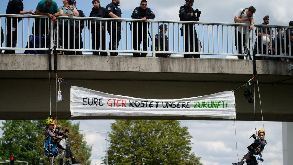 Zwei Kinder seilen sich bei der Klimademonstration in Aachen von einer Brücke ab