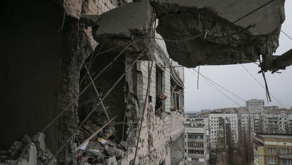 """Ein Mann schaut aus einem von Granatenbeschuss beschädigten Haus in Donezk: """"Alle wollen den Frieden"""""""