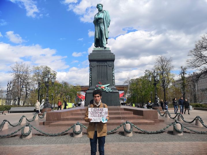 """Makichyan stands in front of the Pushkin memorial in Moscow with a poster reading: """"Climate collapse is coming -- war, hunger, death."""""""