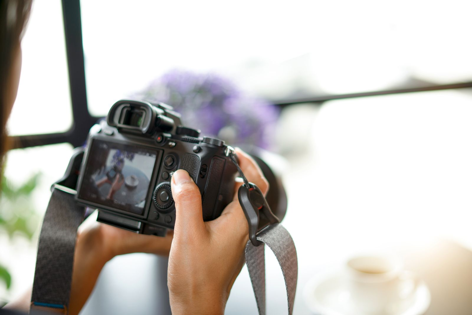 Young woman photographer looking at camera screen sitting at the table with cup of coffee. Concept of occupation and lifestyle.