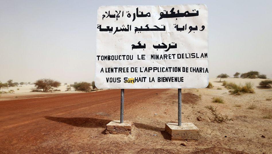 """Ortsschild in Mali: """"Willkommen in Timbuktu: Bei Eintritt Anwendung der Scharia"""""""