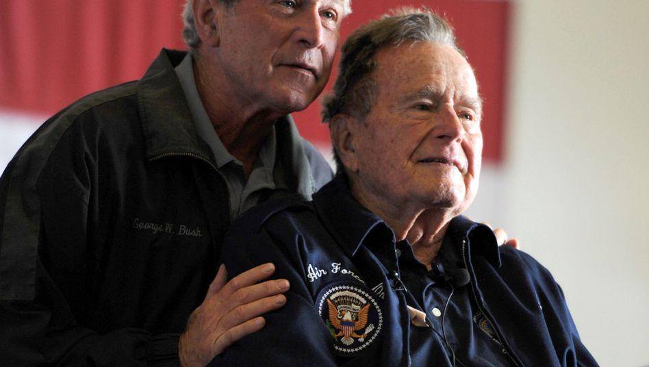 George H.W. Bush and George W. Bush (l.)