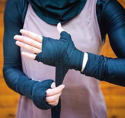Vor einem Kampf umwickelt Zeina ihre Hände mit Bandagen. Das schützt vor Verletzungen