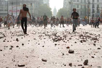Demonstranten marschierten auf einer mit Steinen bedeckten Straße in der Nähe des argentinischen Kongresses