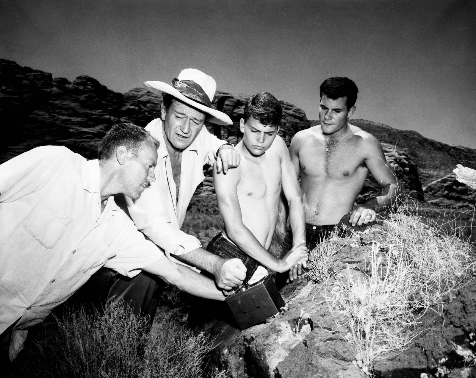 THE CONQUEROR, John Wayne, in hat, with (from left) local Douglas Gentry, sons Patrick Wayne, Michael Wayne, checking ou