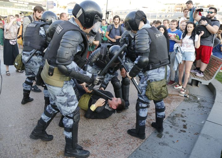 Polizisten halten einen Mann während einer Kundgebung im Zentrum Moskaus fest