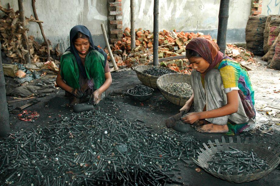 Zwei Mädchen in Bangladesch brechen mit bloßen Händen benutzte Batterien auf
