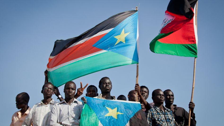 Protestierende mit Flaggen des Südsudans und der Widerstandsbewegung SPLA