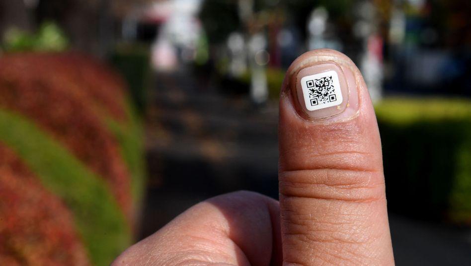 Iruma: QR-Code auf einem Fingernagel