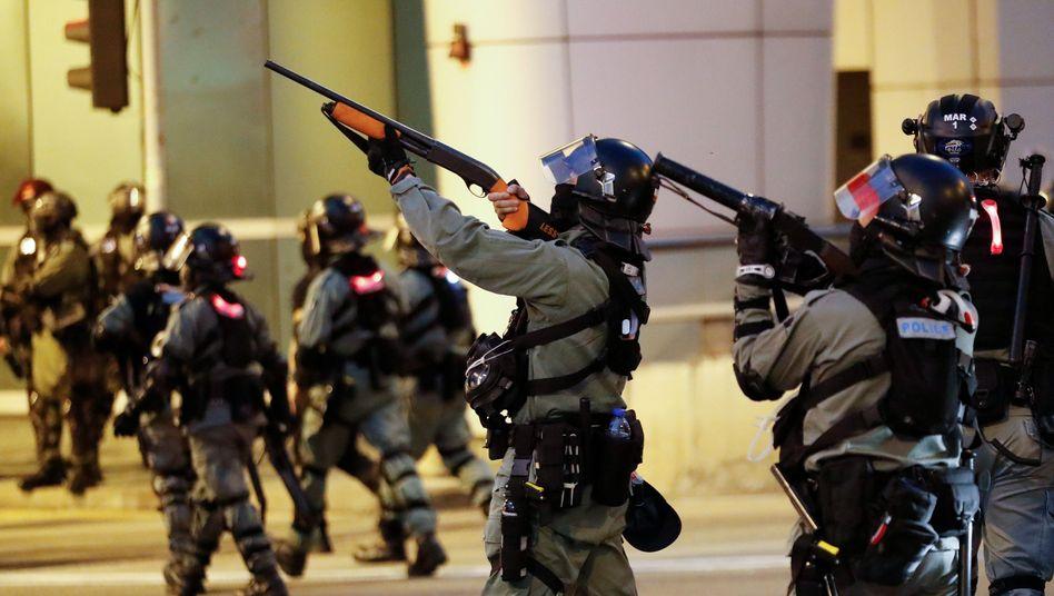 Polizisten zielen während einer prodemokratischen Kundgebung in die Richtung von Demonstranten
