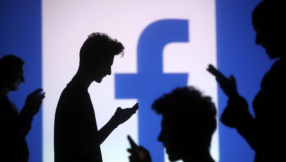 Handynutzer vor Facebook-Logo (Symbolbild): Am Dienstagmorgen war der Zugriff zeitweise nicht möglich