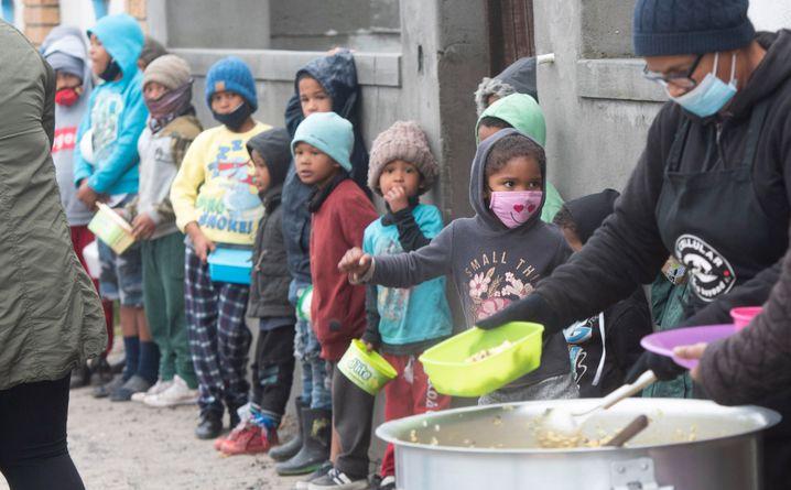 Children standing in line in Michelle Davids' street to receive food handouts.
