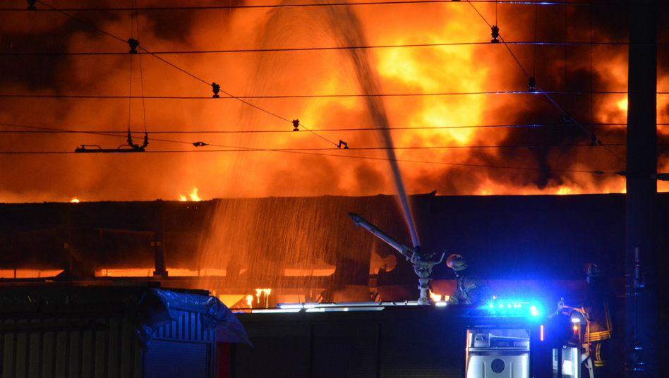 Einsatzkräfte vor der brennenden Halle in Düsseldorf