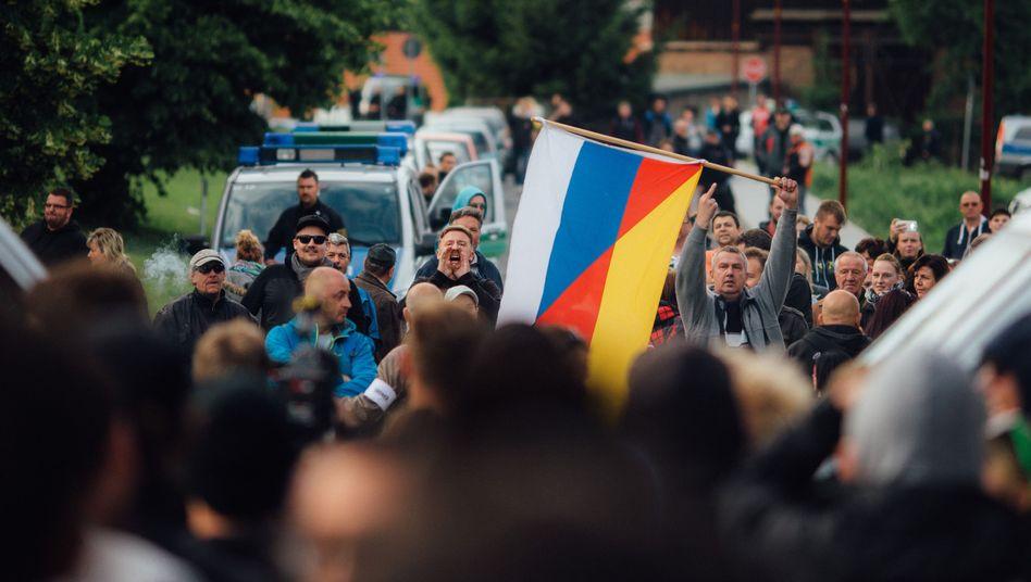 Flüchtlingsgegner mit einer deutsch-russischen Fahne: Die Polizei muss die Unterkunft beschützen