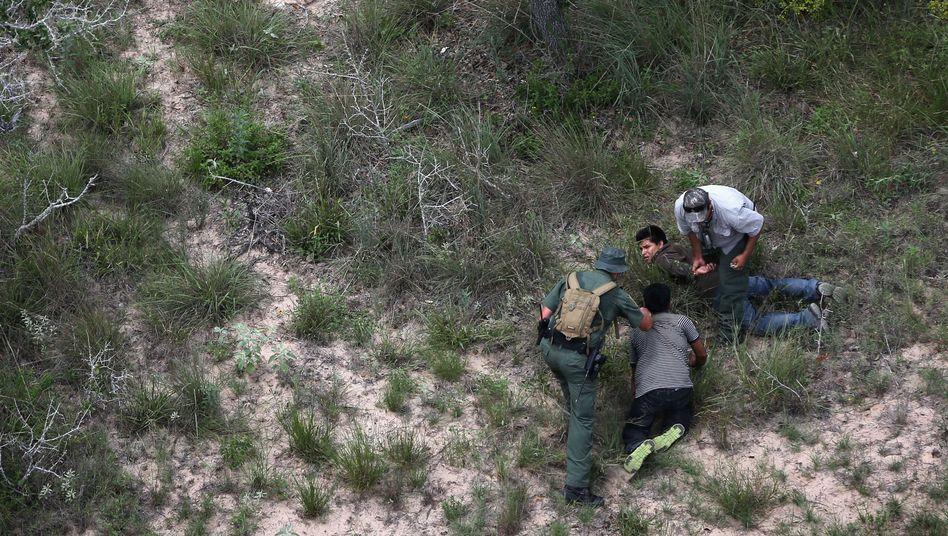 An der Grenze zwischen den USA und Mexiko: Zwei Grenzschützer greifen minderjährige Flüchtlinge auf