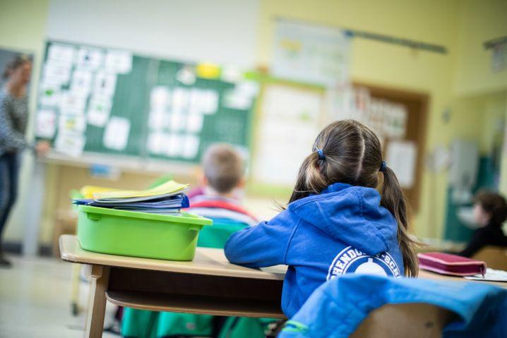 Schülerinnen und Schüler einer Grundschule sitzen mit Abstand in ihrem Klassenraum (Symbolbild)