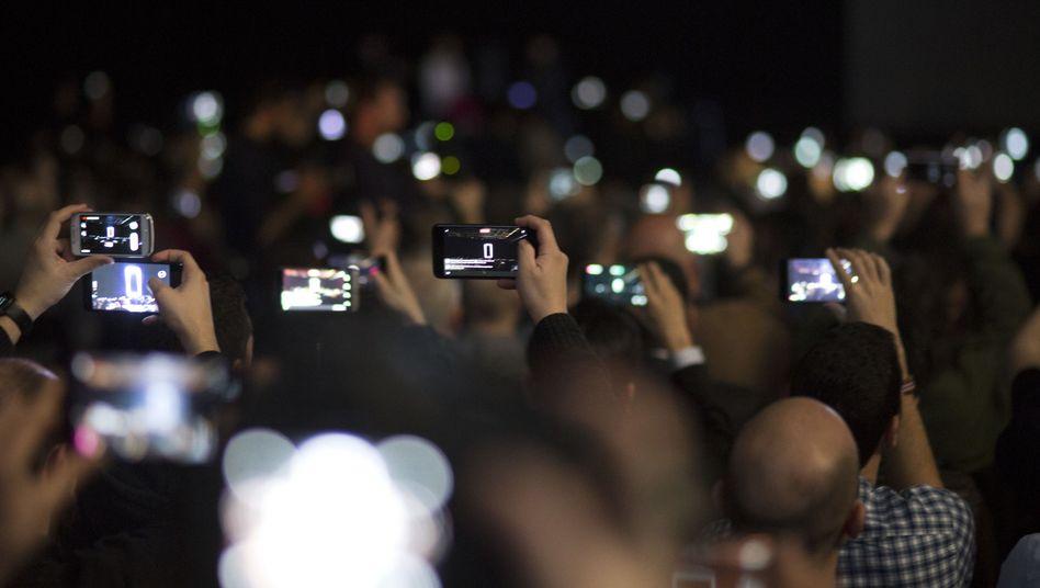 Messebesucher mit Smartphones (Symbolbild)
