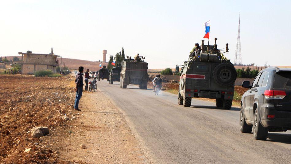 Syrien, Ain al-Arab: Russische Streitkräfte patrouillieren mit gepanzerten Fahrzeugen an der syrischen Grenze