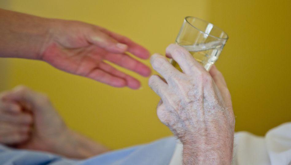 Eine Krankenpflegerin reicht einem Patienten in der Onkologie ein Glas Wasser (Archivbild)