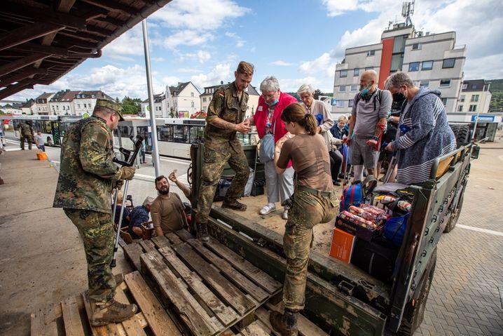 Eine Bundeswehrsoldatin und zwei Bundeswehrsoldaten helfen dabei, ein Krankenhaus in Bad Neuenahr zu evakuieren