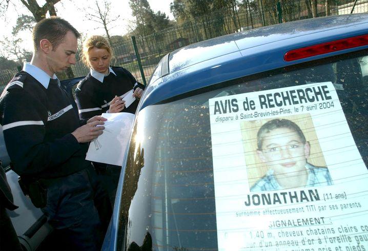 Die Polizei mit einem Vermisstenplakat von Jonathan Coulom im April 2004